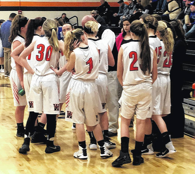 The Lady Wildcats huddle around head coach Steve Smith in the third quarter of their game against the Lady Blue Jays of Ripley on Thursday at Whiteoak High School.