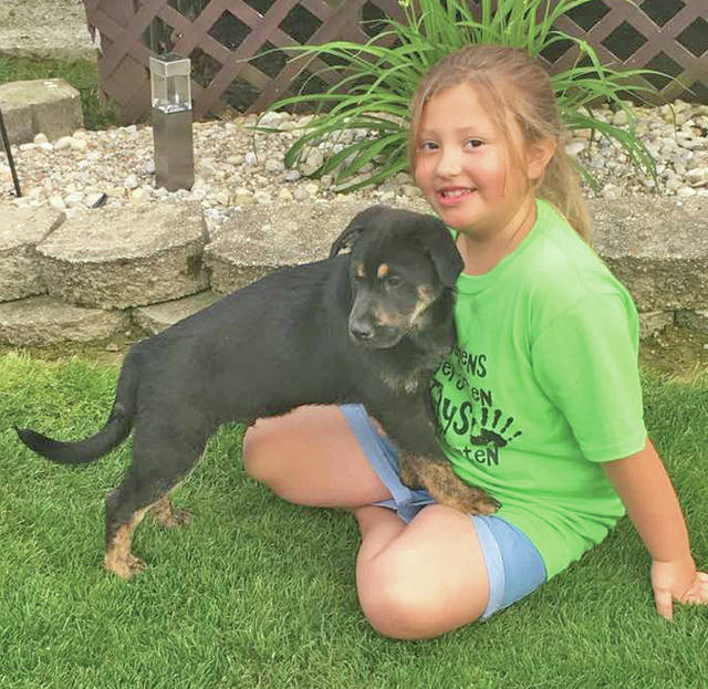 Lynchburg-Clay Elementary first-grader Olivia Furbee is pictured in May 2017 with her puppy.