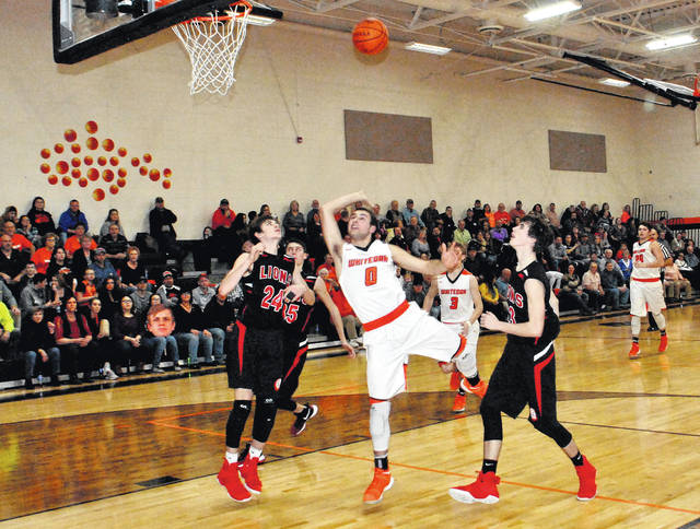 Trevor Yeager (#0) is fouled by Wyatt Willey (#24) as he drives the lane in the third quarter at Whiteoak High School on Tuesday night.