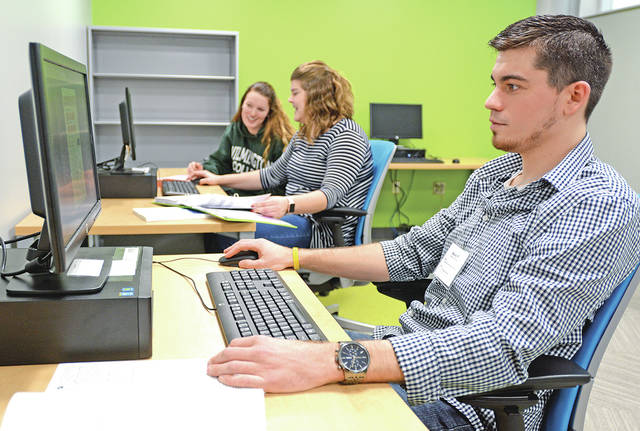 Lynchburg-Clay High School graduate Wesley Pierson works on a tax return at WC's VITA site, along with McClain High School graduate Tara Karnes, center, and Aubrey Richardson, during the 2017 tax season.