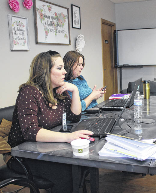 Lynn Goff Clinic staffers Lori Miller, foreground, and Natalia Wright, background, conduct business at the clinic Thursday afternoon.