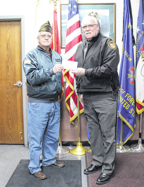 VFW Post 9094 Quartermaster David Pinney, standing in for Commander Rick Wilkin, presents Highland County Sheriff Donnie Barrera with a check on Friday for a new MARCS radio. The radio will be placed in a sheriff's cruiser.