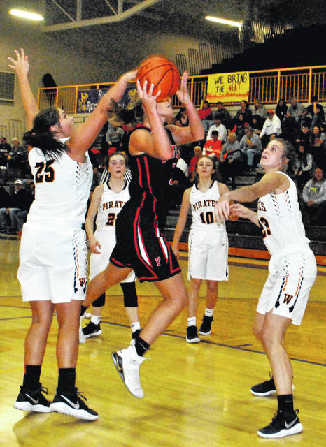 Grace Shope of Fairfield is fouled by a Wheelersburg defender while attempting a layup Saturday at Valley High School as the Lady Lions and Lady Pirates battled for the Division III girls sectional championship.