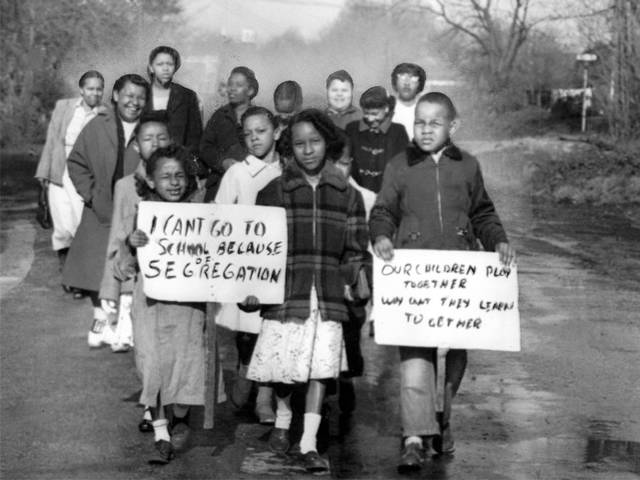 Mothers and children are shown marching in Hillsboro in 1956 to protest school segregation.