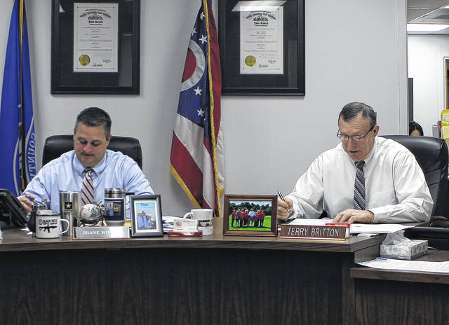Highland County Commissioners Shane Wilkin, left, and Terry Britton discuss business items during a commissioners meeting on Wednesday.
