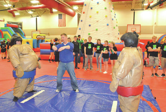"Former volunteer Adam McGinnis, center, gives directions before a pair of ""sumo"" wrestlers square off during a past Hillsboro After Prom Party."