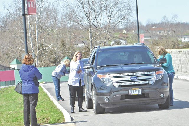Hillsboro City School staff members talk with people arriving to pick up students following a past bomb threat at the high school/middle school.