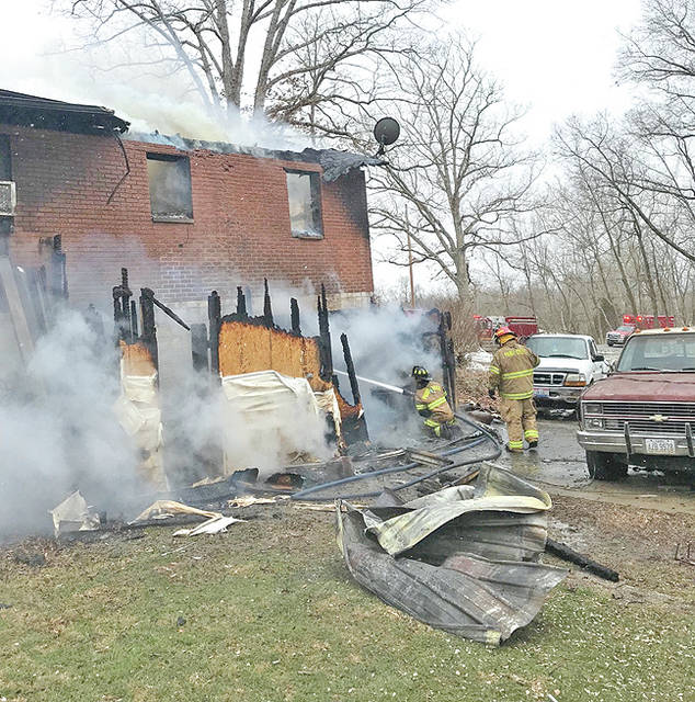 Firefighters work to extinguish a blaze on the back side of a home Wednesday on Coss Road. The home was ruled a total loss.