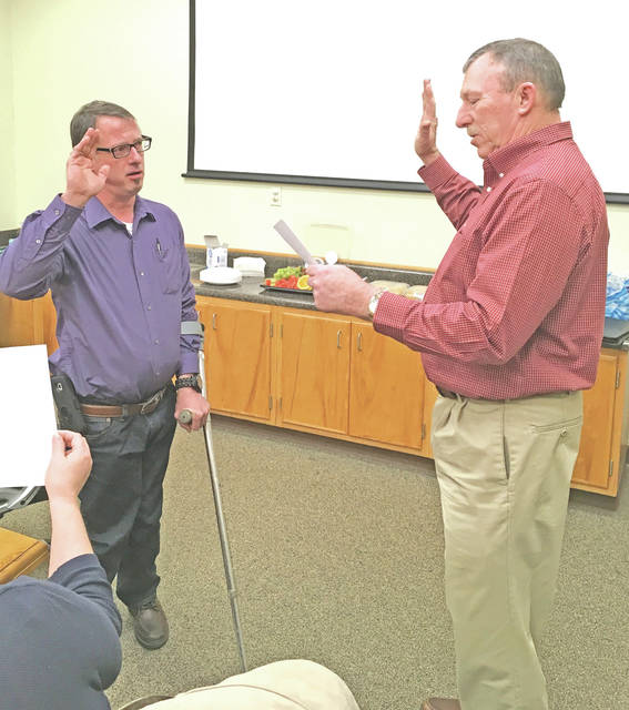 Michael Richards, left, the newest member of the Highland County Board of Developmental Disabilities, is sworn in by Highland County Commissioner Terry Britton.