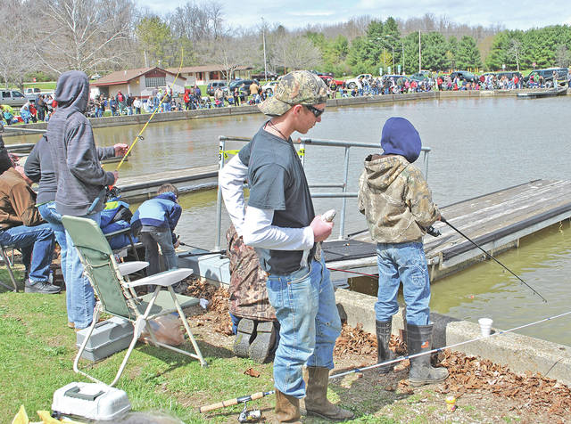 A youngster holds a trout he just caught while part of the rest of the crowd is shown during the 2016 Highland County Rod and Gun Club Kids Trout Derby at Rocky Fork State Park.