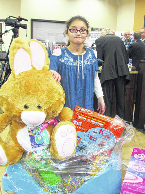Emily Davis, one of the poster children for this year's Ernie Blankenship Memorial Radio-Telethon for the benefit of the Highland County Society for Children and Adults, poses with gifts presented by the Hillsboro Eagles at Wednesday night's event at NCB Bank in Hillsboro.