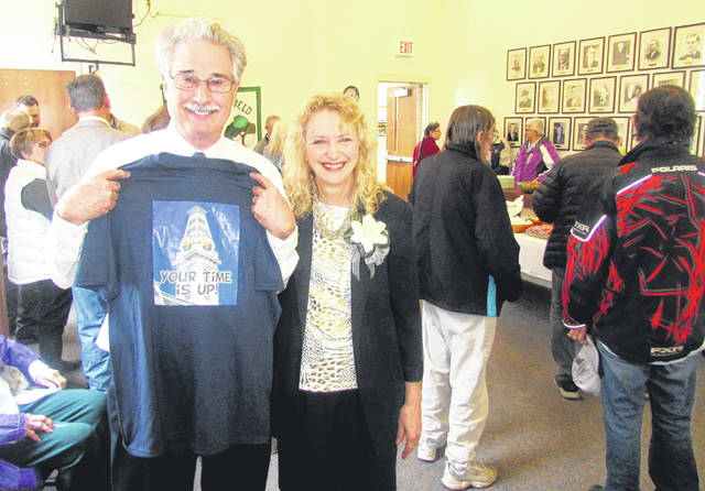 """Ron Coffey and his wife, Dianna, pose for a picture Friday at a farewell open house as Coffey holds up a t-shirt with a picture of the clock atop the Greenfield city building featuring his face in the clock tower with the caption, """"Your time is up!"""""""