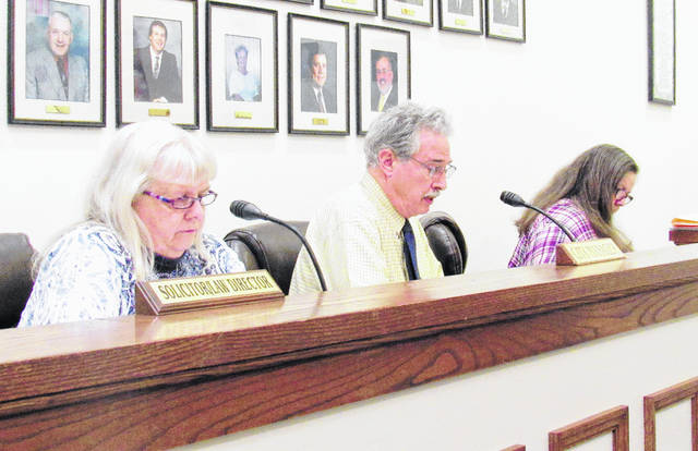 Greenfield Finance Director Carolyn Snodgrass, left, and council clerk Roberta Karnes, right, are shown with City Manager Ron Coffey as he gives his report during Wednesday's council meeting.