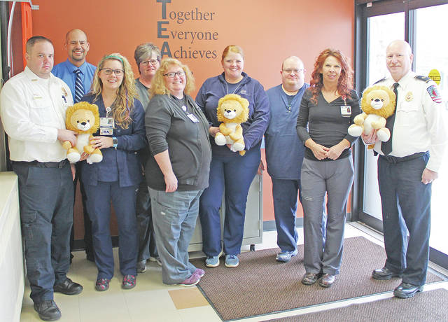 Adena Greenfield Medical Center leaders and emergency department caregivers are shown with officers from Rescue 101 Search and Rescue and donated Rory the Lion toys.