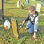 Johnathan Naylor is shown cleaning a gravestone last fall at the Cherry Fork Cemetery.
