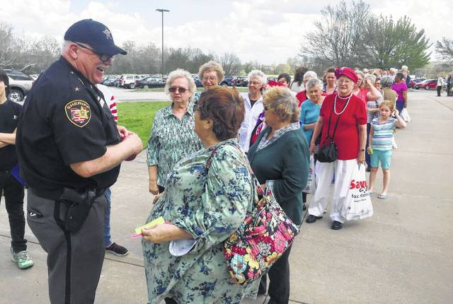Highland County Sheriff Donnie Barrera, left, is shown distributing free door prize tickets to guests as they arrive at a previous Salt Homemakers Show. Guests who bring five non-perishable food items Thursday for the Highland County Homeless Shelter get one door prize ticket, and those who bring 10 items get three tickets.