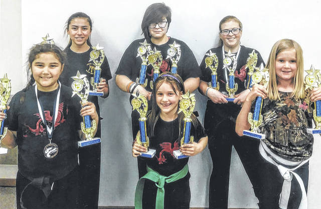 The members of the Cross County Bushido Karate Club of Highland, Ohio show off trophies that they won at a tournament in Jackson, Ohio.
