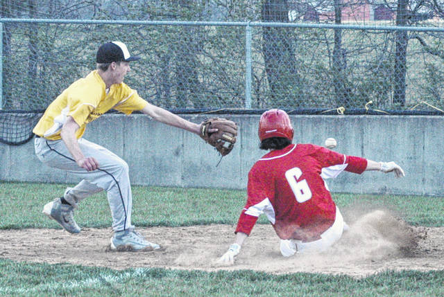 Hillsboro's Luke Magulac slides across home plate as Lynchburg-Clay's Caden Hess maintains his position while trying to make a play.