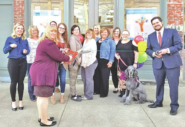 Heather Gibson, CEO of REACH for Tomorrow, cuts the ribbon during a ceremony celebrating joining the Highland County Chamber of Commerce held at the Greenfield facility last month.