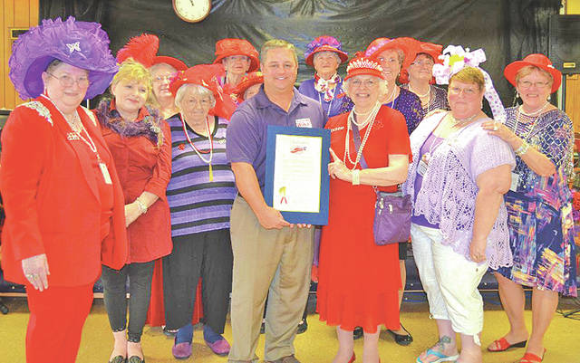 The Hillsboro Annual Spring Fling was a huge success. One hundred and fifteen Red Hatters attended the event at the Highland County Senior Citizens Center, and the food was good, hot served by volunteers from the community. The picture shows Highland County Commissioner Shane Wilkin reading a proclamation celebrating the Red Hat Society's 20-year anniversary in the city of Hillsboro on April 25. The Precious Pearls proclaimed April 25 Red Hat Society Day in Hillsboro.