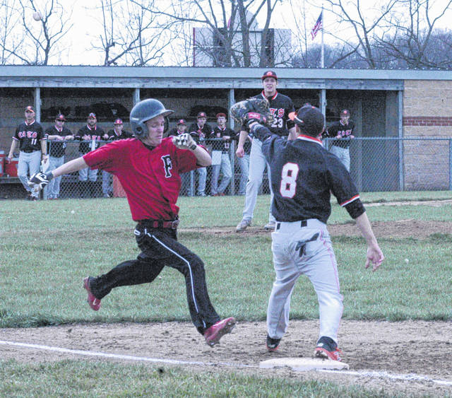 Austin Setty of Fairfield tried to beat the throw to Whiteoak first baseman Ryan Roberts as Wildcats Pitcher Evan Brill looks on from the mound on Thursday at Fairfield High School.