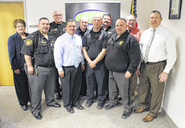 Shown from left, back row, are Paint Valley ADAMH Board Executive Director Penny Dehner, Highland County Sheriff Donnie Barrera, Michael Sowards of the Paint Creek Joint EMS/Fire District, HCSO Chief Deputy Brandon Stratton and Commissioner Jeff Duncan. Shown from left, front row, are HCSO Lt. Keith Brown, Commissioner Shane Wilkin, Michael Glenn of Paint Creek, HCSO Deputy Mike Gaines and Commissioner Terry Britton.