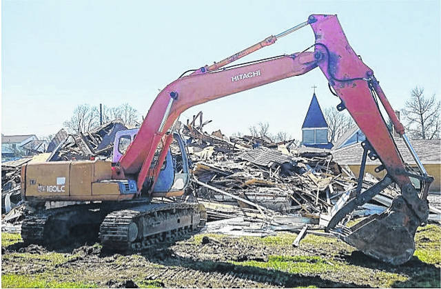 A piece of heavy equipment stands near the remains of the old parsonage building near the Greenfield Church of Christ last week.