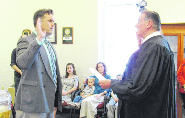 Todd Wilkin, left, is admnistered the oath of office by Highland County Court (Greenfield) Judge Robert Judkins during a ceremony Friday morning in the village council chambers.