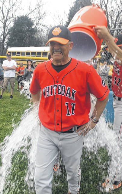 Whiteoak Wildcats' head baseball coach Chris Veidt has the water cooler poured on him by his team at Peebles High School on Friday where the Wildcats wrapped up an undefeated SHAC season at 13-0 and a 22-1 record overall.