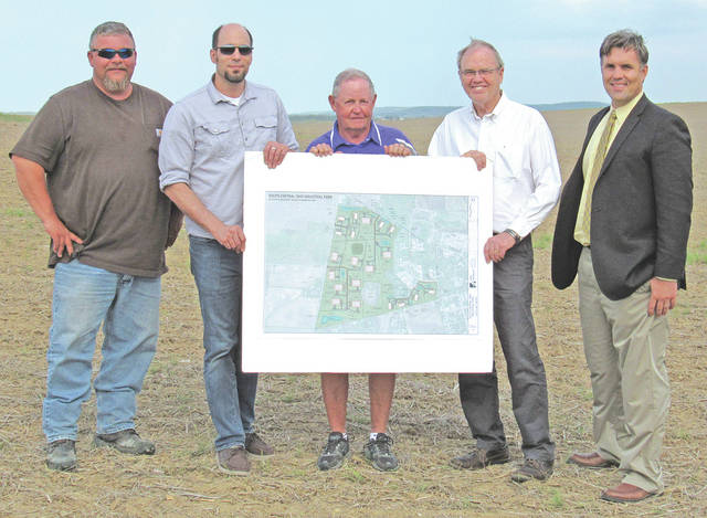 On a breezy afternoon Greenfield Council members (l-r) Chris Borreson, Eric Borsini, Bob Bergstrom and Phil Clyburn, as well as city manager Todd Wilkin (far right), gathered on the undeveloped west end of the Greenfield's industrial park. They are holding a diagram of the site plan for the park, which has recently become certified with the state, increasing its visibility to prospective businesses.