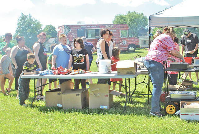 Visitors wait their turn to receive a free lunch during the HCS Tomahawk Food Truck Summer Kickoff event held Thursday at the old school site off West Main Street in Hillsboro. The truck that will deliver lunches to nine locations weekdays this summer is pictured in the background.