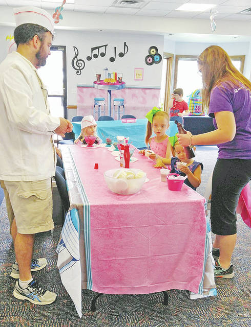 Krystal Swan and her daughters enjoy the Greenfield Library Summer Readers Soda Shop kickoff.