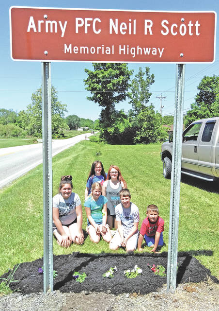 Members of the Highland County Buckeyes 4-H Club are pictured beneath one of four highway veterans memorial signs in Highland County where they recently mulched and planted flowers. Lowe's, TSC and Walmart made donations to the club to help purchase the flowers and mulch. The sign shown in this photograph is located on Willetsville Pike.
