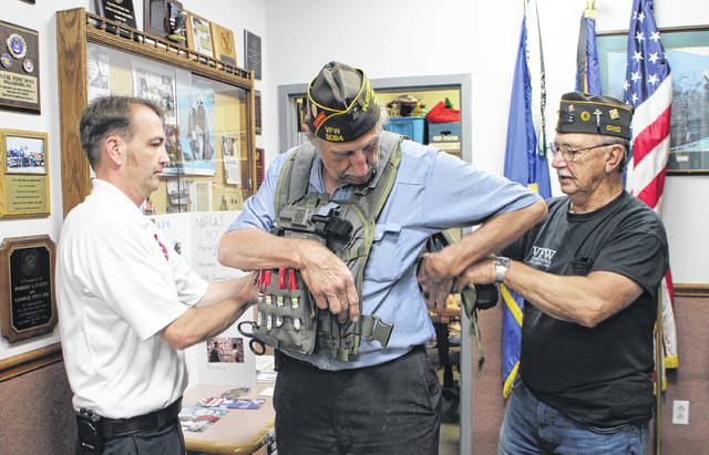 Hillsboro VFW Post 9094 Commander Rick Wilkin, center, tries on a ballistic medic vest this week at the post as Lynchburg Area Joint Fire and Ambulance District Chief Jeff Turner, left, and Sr. Vice Commander Dwight Reynolds, right, lend a helping hand.