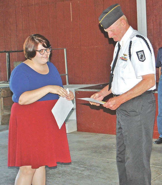 Several local veterans organizations were honored Thursday during Flag Day ceremonies held at AMVETS of Hillsboro Post 61 for their contributions, financially and as volunteers, to the Georgetown Veterans Home. In this photo, Jim Vinson, acting as commander for the Highland County Veterans Honor Guard, accepts an award from Hanna Hopper, volunteer services coordinator at the veterans home.