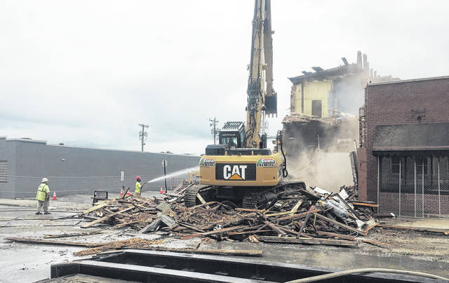Demolition crews are shown tearing down the former Armintrout law office building on Governor Trimble Place in Hillsboro on Thursday.