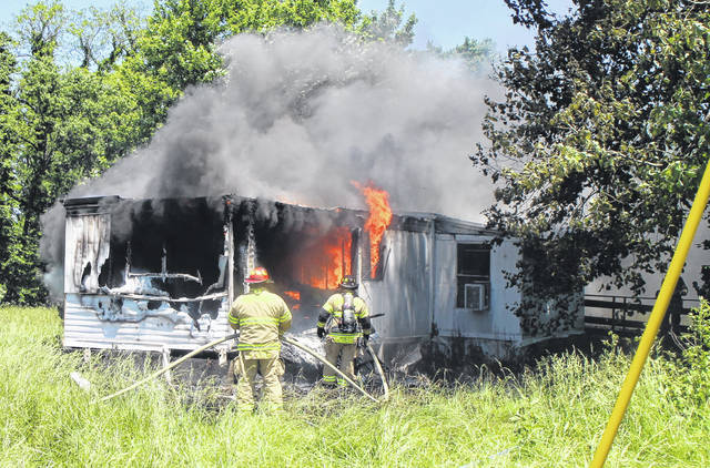 Firefighters spray down a single-wide trailer at a farm on U.S. Route 50 east of Hillsboro Monday afternoon.