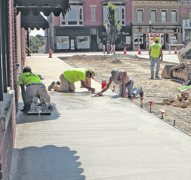 Construction workers finish a new sidewalk on Thursday in front of businesses along Gov. Trimble Place in Hillsboro.