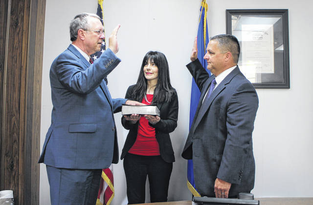 Gary Abernathy, publisher and editor-in-chief of The Times-Gazette, left, is sworn in Thursday as a Highland County Commissioner by State Rep. Shane Wilkin, right. Abernathy's wife, Lora, is shown holding the Abernathy's family Bible.