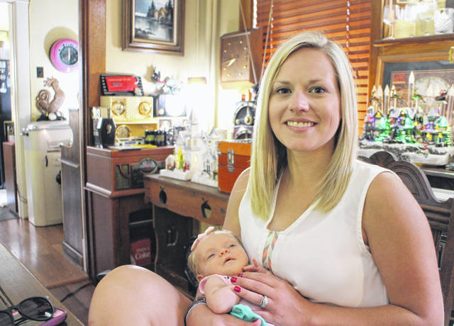Amanda Hunter is shown with her one-month-old daughter, Reese, at the St. Mary Catholic Church rectory.
