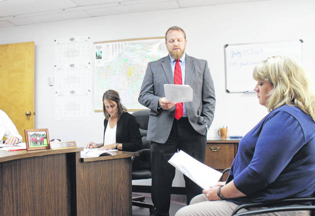 Highland County Health Commissioner Jared Warner, standing, speaks to county commissioners on Wednesday. Also shown are Highland County Commission Clerk Mary Remsing, left, and Highland County Health Department Fiscal Officer Connie Page, right.