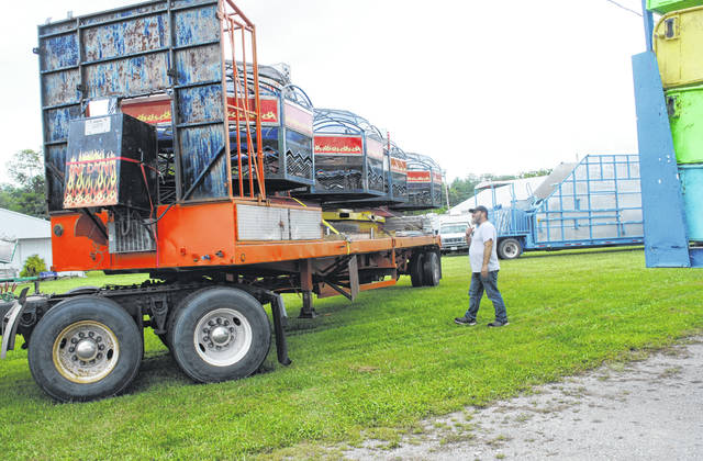 Valdon Gorham, manager of Cromer Amusements, directs a trator-trailer rig as it maneuvers to put a ride in place Thursday afternoon at the Highland County Fairgrounds.