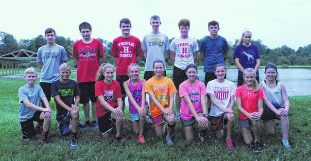 Members of the Hillsboro boys and girls varsity Cross Country team pose for a group photo at Harmony Lake in Hillsboro.