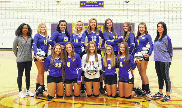 The McClain Lady Tigers varsity Volleyball team poses for a group photo with their coaches in the McClain High School gym.
