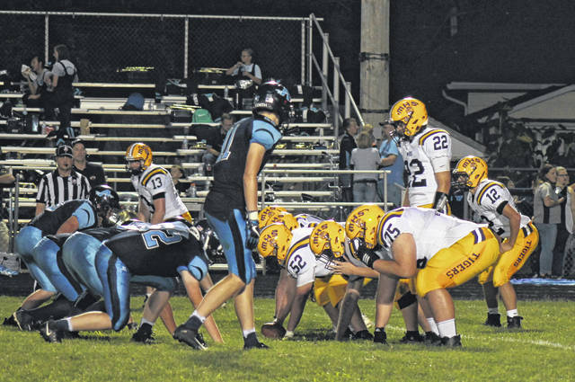 McClain starting quarterback Dalton Mischal surveys the defense before snapping the ball Friday night at Adena High School in the Tigers' opening game of the season.