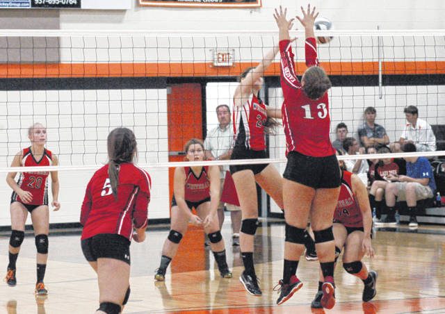 Whiteoak's Macy Knoblauch (24) and Eastern's Mia Rockey (13) meet at the net during the first set of the Lady Wildcats' match against the Lady Warriors on Thursday at Whiteoak High School.