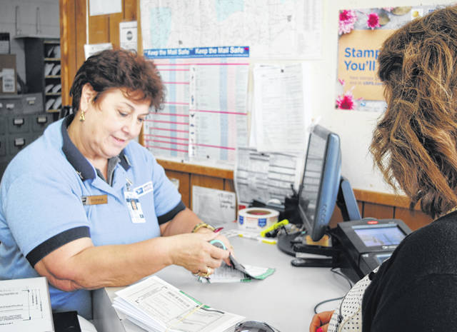 Donna Allen takes care of a customer at the Hillsboro Post Office last week.