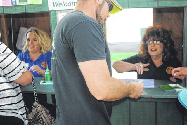 Hillsboro Rotary Club members Mechell Frost, left, and Sharon Hughes, right, run the ticket booth at the 2018 Highland County Fair last week as a fairgoer obtains his pass.